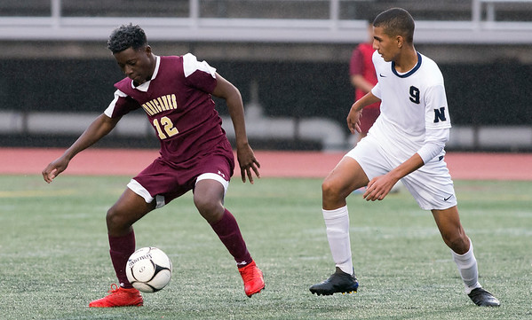 10/29/19 Wesley Bunnell | StaffrrNew Britain soccer was defeated 2-0 by Newington during a drizzle at Veterans Stadium on Tuesday afternoon. New Britain's Devoy Samuels (12) and Newington's Adam Khadrani (9).