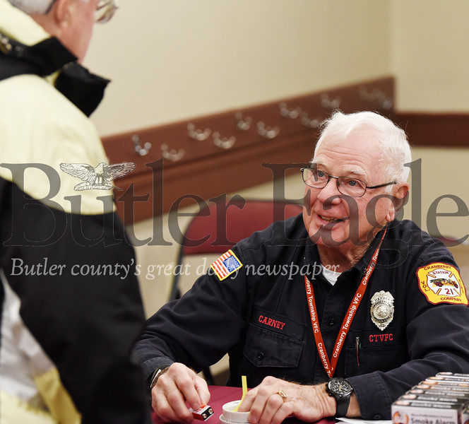 Harold Aughton/Butler Eagle: Jack Carney, a Cranberry Township Volunteer Fireman, discusses the importance of senior of replacing their fire detectors with Cranberry resident, Jim Ofriel, Wednesday, Dec. 11, 2019. The CTVF Company handed out free fire detectors to senior citizens of Cranberry Twp. at the Municipal Center. The department raised $3,000 to purchase 700 fire detectors at a discounted cost from Home Depot.