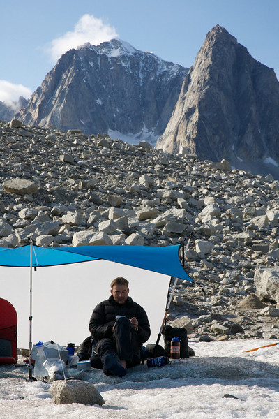 Mark is a dutiful note taker.  Here he enjoys tarp time, sunshine, and solitude high on the Fish Creek Glacier - Revelation Mountains, Alaska.