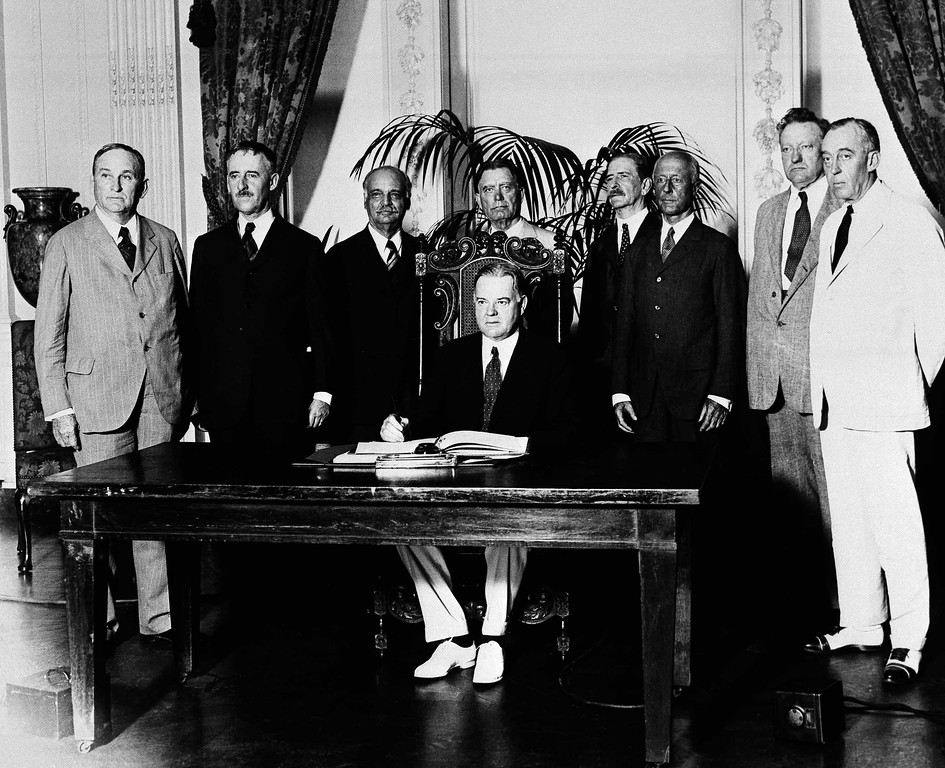 . The London Treaty was ratified in Washington, July 22, 1930, with President Herbert Hoover\'s signature.  Shown after the signing are, from left to right:  Sen. Joseph Taylor of Ark.; Secretary of State Henry Stimson; Vice President Charles Curtis; Sen. William E. Borah of Idaho; Naval Secretary Charles F. Adams; Sen. James Eli Watson of Indiana; Sen. David A. Reed of Pennsylvania.  Hoover is seated at desk.  (AP Photo)