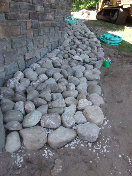 Rocks along drip lines of house to reduce erosion of soil