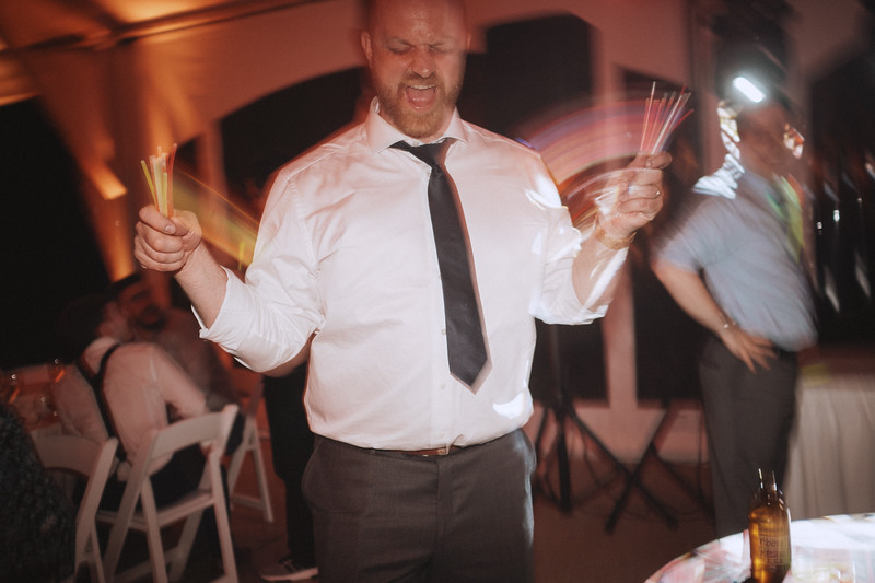 The groom sings at the top of his lungs while he waves fist fulls of glow sticks in both hands.