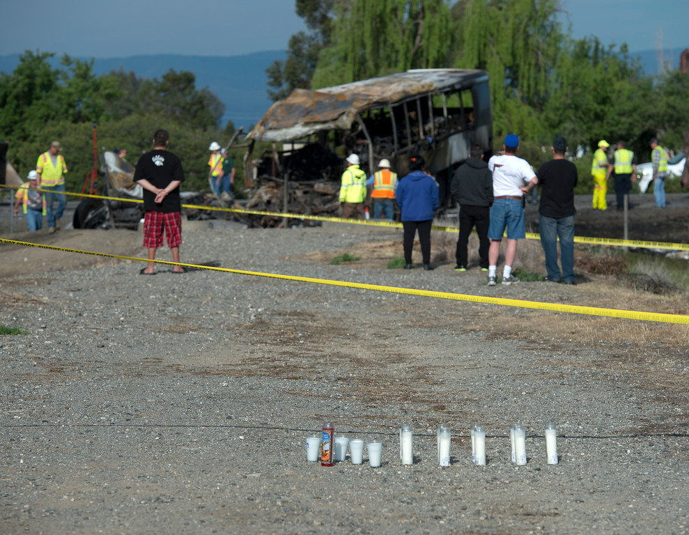 . Candles and flowers are seen at a make-shift memorial, Friday, April 11, 2014, for the victims of a multi-vehicle accident that included a tour bus and a FedEX truck crashed on Interstate 5  in Orland, Calif.  Ten people were killed and dozens injured in the fiery crash, Thursday, between the truck and a bus seen in background, carrying high school students on a visit to a Northern California College. (AP Photo/The Sacramento Bee, Hector Amezcua)  MAGS OUT; LOCAL TV OUT (KCRA3, KXTV10, KOVR13, KUVS19, KMAZ31, KTXL40); MANDATORY CREDIT
