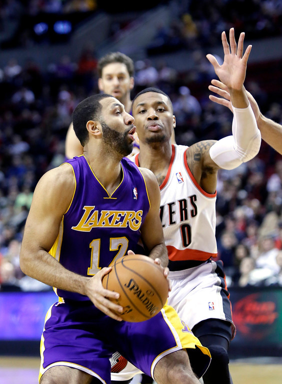 . Los Angeles Lakers guard Kendall Marshall, left, looks to shoot against Portland Trail Blazers guard Damian Lillard during the first half of an NBA basketball game in Portland, Ore., Monday, March 3, 2014. (AP Photo/Don Ryan)