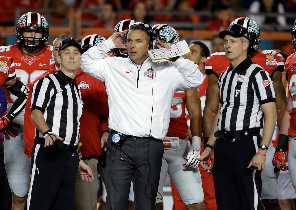 . Ohio State coach Urban Meyer stands with officials as they wait for a ruling on the field during the first half of the Orange Bowl NCAA college football game against Clemson, Friday, Jan. 3, 2014, in Miami Gardens, Fla. (AP Photo/Lynne Sladky)