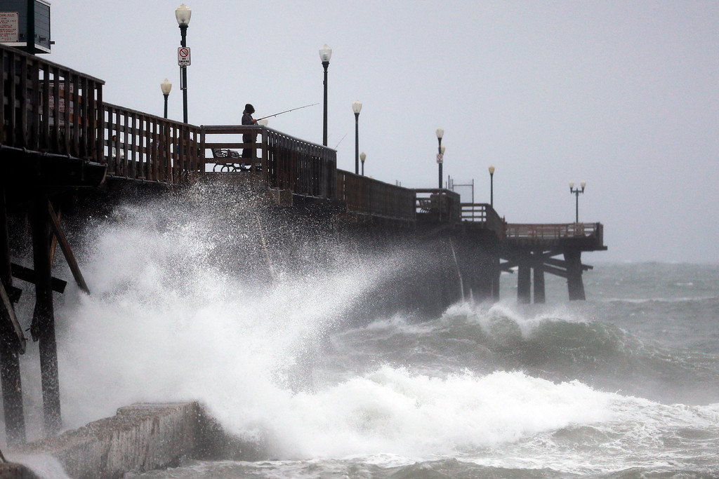 . Waves crash against a pier Friday, Feb. 17, 2017, in Seal Beach, Calif. A major Pacific storm has unleashed downpours and fierce gusts on Southern California, triggering flash flood warnings and other problems. (AP Photo/Jae C. Hong)