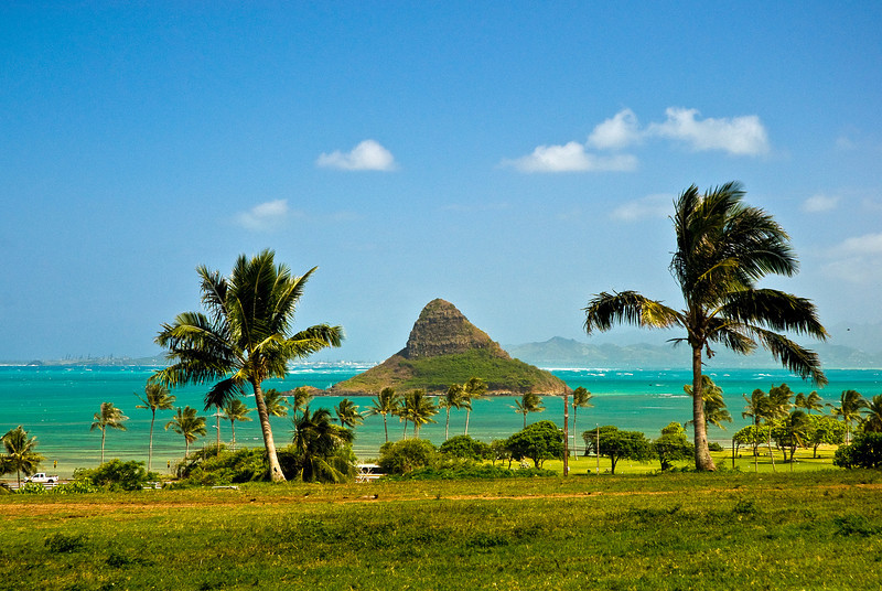 """Mokolii Island's nickname, """"Chinaman's Hat"""" came  from its conical shape resembling the straw coolie hats  used by immigrant workers.  It is said that Chinaman's Hat is the remains of a  giant mo'o (lizard god). The island is most accessible  from the state's Kualoa Regional Beach Park.  Getting to the island is up to you. Obviously, this  requires crossing a body of water in some manner:  kayaking, swimming, snorkeling, boating, etc.  The island trail is a short but challenging 206-foot  climb to the top.  Windward, O'ahu"""