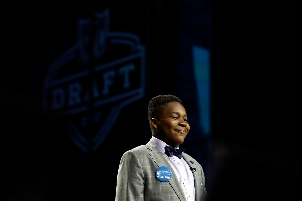 . T.J. Owuanibe, 14, smiles as he walks to announce the Baltimore Ravens\' selection during the first round of the 2017 NFL football draft, Thursday, April 27, 2017, in Philadelphia. (AP Photo/Matt Rourke)
