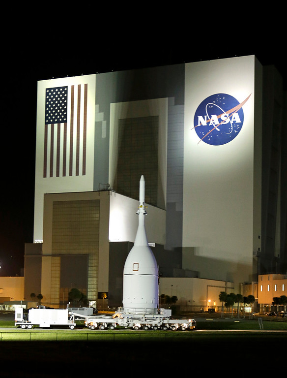. The Orion Spacecraft moves by the Vehicle Assembly Building on its approximately 22 mile  journey from the Launch Abort System Facility at the Kennedy Space Center to Space Launch Complex 37B at the Cape Canaveral Air Force Station, Tuesday, Nov. 11, 2014, in Cape Canaveral, Fla. The test flight for Orion is scheduled to launch on Dec. 4.(AP Photo/John Raoux)
