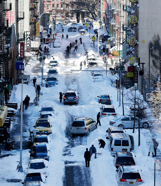 . People clear snow from parked cars on Henry Street in the Chinatown neighborhood in New York on Sunday, Jan. 24, 2016. Millions of Americans began digging out Sunday from a mammoth blizzard that set a new single-day snowfall record in Washington and New York City. (AP Photo/Peter Morgan)