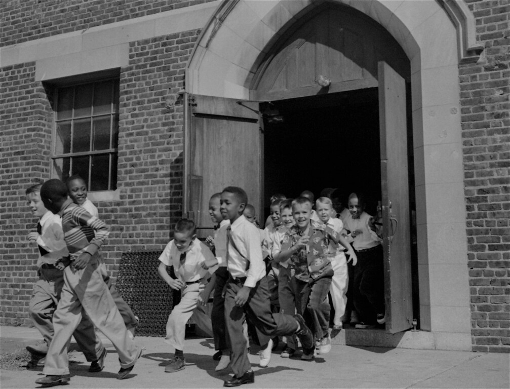 . Black and white fourth graders at St. Martin School, Washington, DC, dash for the playground at recess, September 17, 1954.  While the District of Columbia and four states acted to end segregation in the schools, other states either resisted the Supreme Court\'s desegregation ruling of last May, or waited for a decision, due this fall, on ways to carry out the ruling.  (AP Photo)