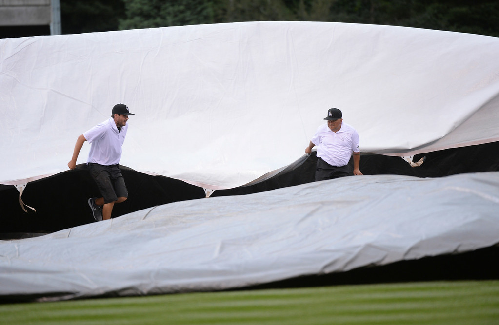 . DENVER, CO - JUNE 20: Two members of the Coors  Field grounds crew pulled the tarp onto the field Saturday afternoon. The start of the game was delayed at least thirty minutes. The Colorado Rockies hosted the Milwaukee Brewers at Coors Field Saturday afternoon, June 21, 2014. Photo by Karl Gehring/The Denver Post