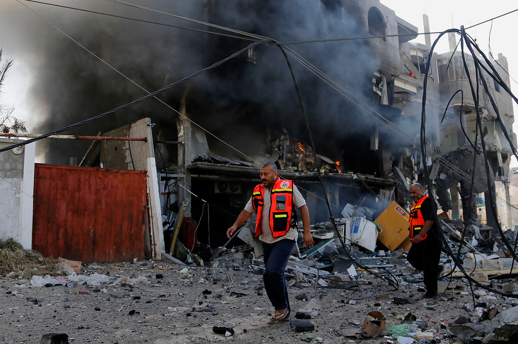 . Palestinian firefighters inspects the damage of a destroyed milk factory after it was hit by an Israeli airstrike in Gaza City, Thursday, July 31, 2014. Israel said Thursday it has called up another 16,000 reservists, allowing it to potentially widen its Gaza operation against the territory\'s Hamas rulers in a three-week-old war that has killed more than 1,300 Palestinians and more than 50 Israelis. (AP Photo/Hatem Moussa)