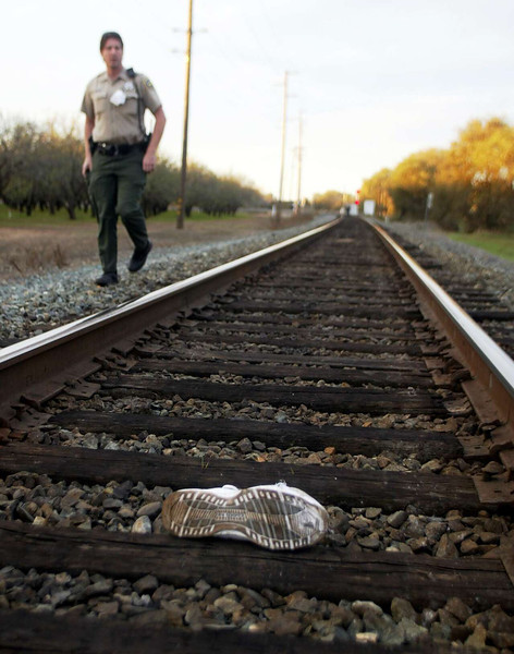 Sheriff Joel Malinowski walks down the tracks near a shoe belonging to a man who was hit by a train just south of the Hegan Lane RxR crossing Sunday afternoon. - halley photo 11/27/05