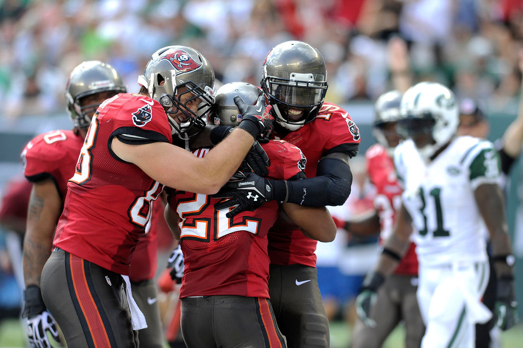 . Tampa Bay Buccaneers running back Doug Martin (22) is congratulated by teammates Luke Stocker, left, and Mike Williams after scoring a touchdown against the New York Jets in the first half of an NFL football game, Sunday, Sept. 8, 2013, in East Rutherford, N.J. (AP Photo/Bill Kostroun)