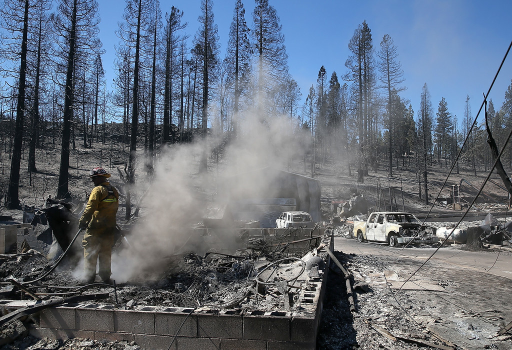 . A firefighter cools off hot spots in the remains of a destroyed home on September 16, 2014 in Weed, California. A fast moving wildfire fueled by high winds ripped through the town of Weed on the afternoon of September 15, burning 100 structures including the high school and lumber mill.  (Photo by Justin Sullivan/Getty Images)