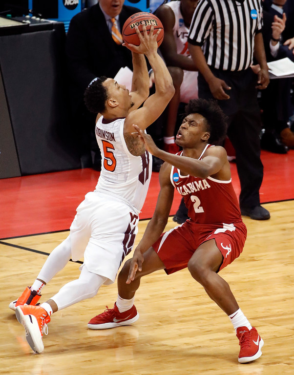 . Justin Robinson (5) draws an offensive foul on Alabama \'s Collin Sexton (2) during the second half of an NCAA men\'s college basketball tournament first-round game, in Pittsburgh, Thursday, March 15, 2018. Alabama won 86-83. (AP Photo/Gene J. Puskar)