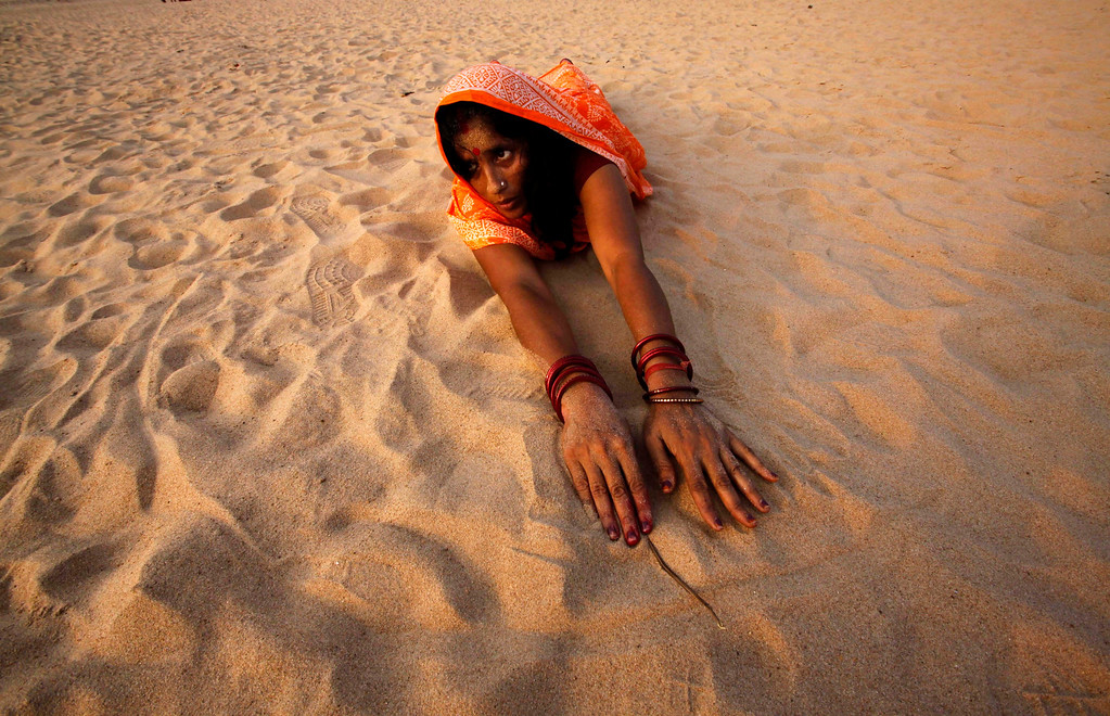 . A Hindu woman devotee makes her way towards the Kathajodi River in a prostrating position as part of rituals during Chhath Puja festival near Cuttack, India, Friday, Nov. 8, 2013.  (AP Photo/Biswaranjan Rout)
