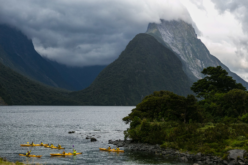 Kayaks in the water in Milford Sound surrounded by tall mountains.