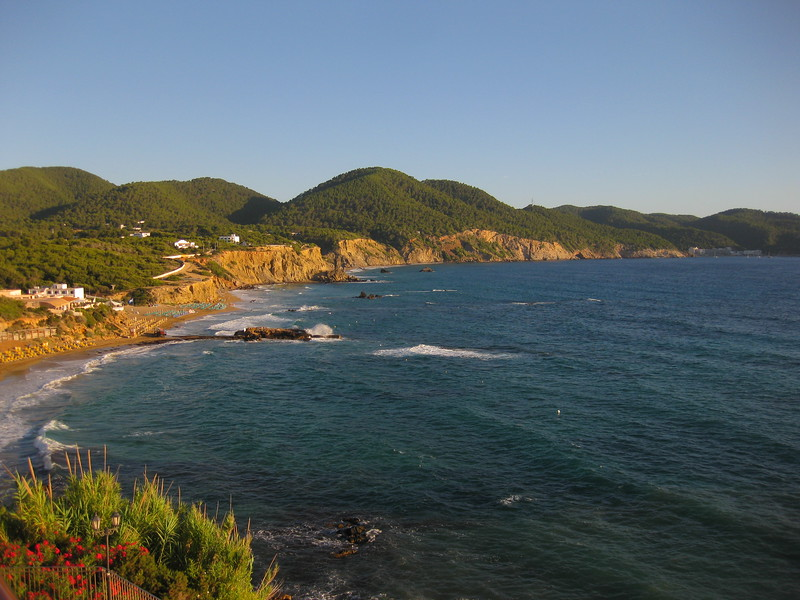 Green covers the low mountains of ibiza's coastline.