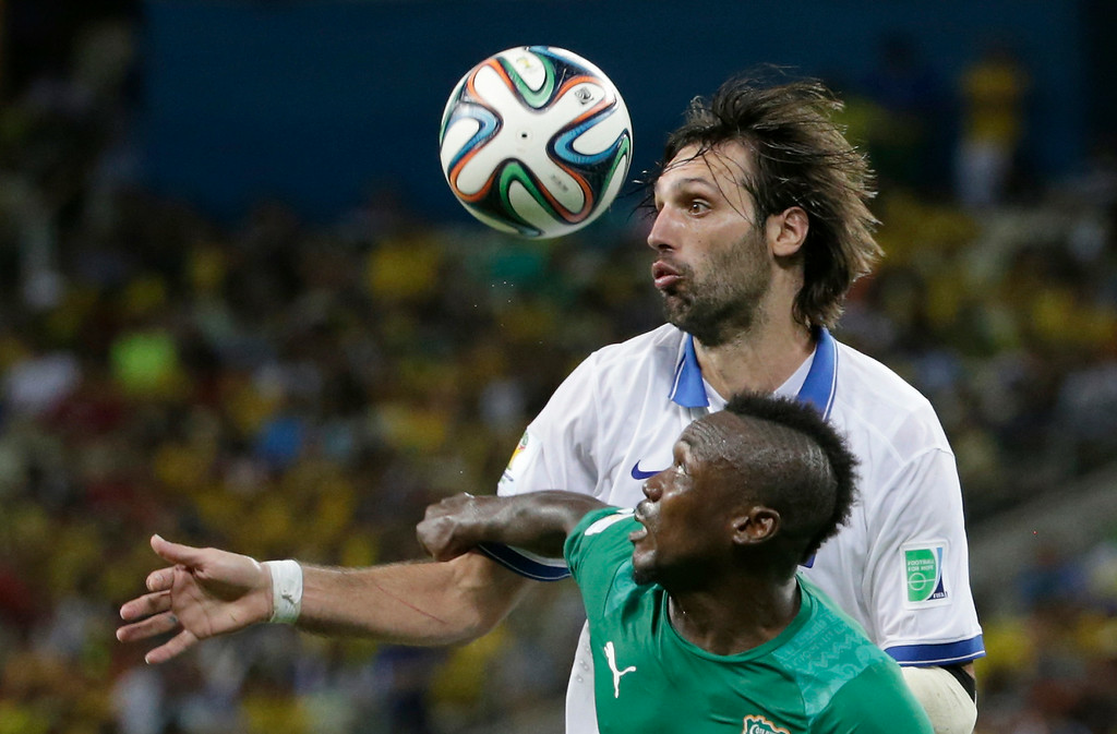 . Ivory Coast\'s Arthur Boka, front, and Greece\'s Giorgos Samaras challenge for the ball during the group C World Cup soccer match between Greece and Ivory Coast at the Arena Castelao in Fortaleza, Brazil, Tuesday, June 24, 2014. (AP Photo/Fernando Llano)