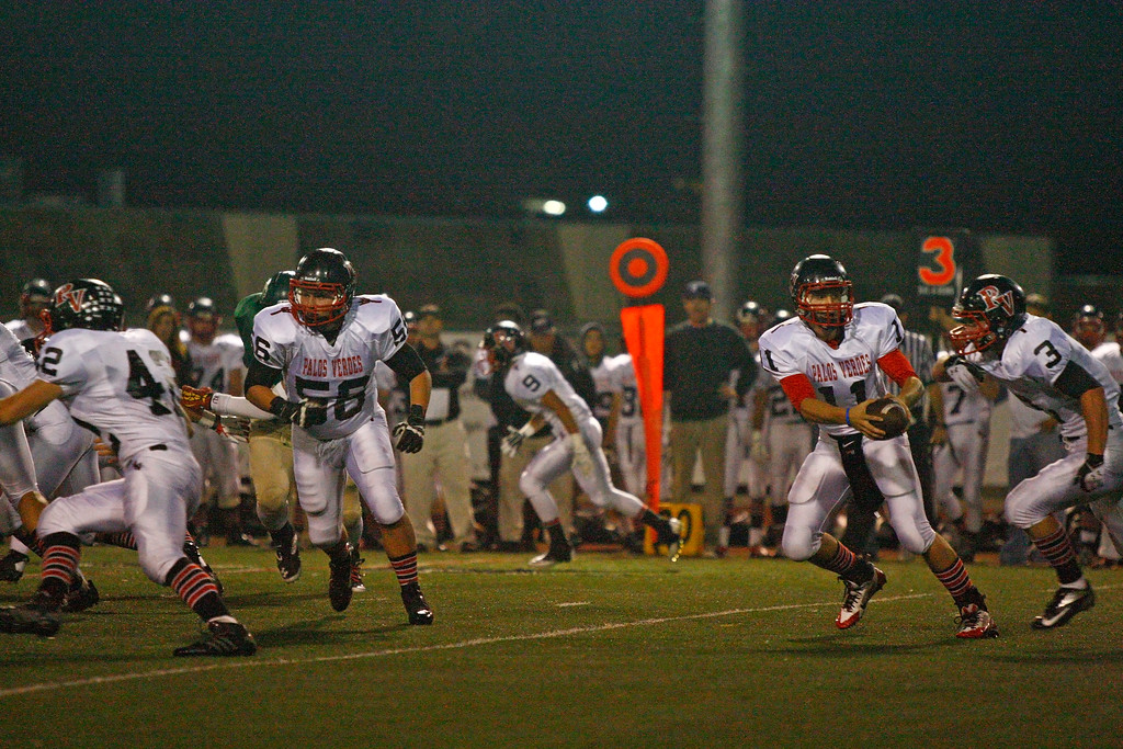 . Quarterback Daniel DiRocco #11 of Palos Verdes hands the ball off to Tyler Moore #3 against the defense of Mira Costa in a Bay League matchup at Mira Costa High School on Friday, October 18, 2013 in Manhattan Beach, Calif.  (Michael Yanow / For the Daily Breeze)