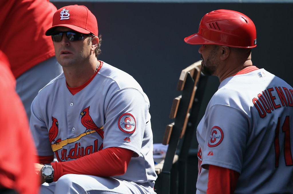 . Manager Mike Matheny #22 of the St. Louis Cardinals and third base coach Jose Oquendo #11 of the St. Louis Cardinals talk in the dugout as they face the Colorado Rockies at Coors Field on September 19, 2013 in Denver, Colorado.  (Photo by Doug Pensinger/Getty Images)