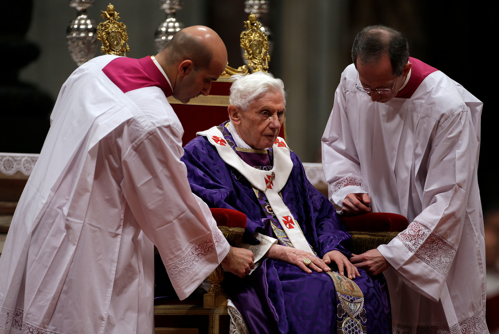 "Description of . Bishop Guido Marini, right, and an unidentified master of ceremonies adjust Pope Benedict XVI\'s robe during the Ash Wednesday mass in St. Peter\'s Basilica at the Vatican, Wednesday, Feb. 13, 2013.  Ash Wednesday marks the beginning of Lent, a solemn period of 40 days of prayer and self-denial leading up to Easter. Pope Benedict XVI told thousands of faithful Wednesday that he was resigning for ""the good of the church\"", an extraordinary scene of a pope explaining himself to his flock that unfolded in his first appearance since dropping the bombshell announcement. (AP Photo/Gregorio Borgia)"