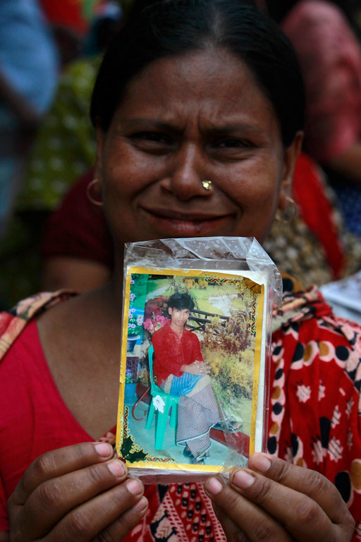 . A relative holds a picture of a missing garment worker, who was working in the Rana Plaza building when it collapsed, in Savar, 30 km (19 miles) outside Dhaka April 24, 2013.  REUTERS/Andrew Biraj