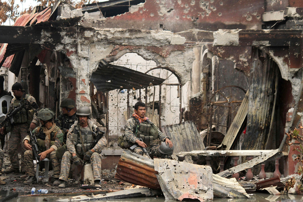 . Government troops rest amidst the ruins at the site of a three-week standoff in Zamboanga city, southern Philippines, Saturday, Sept. 28, 2013. The deadly standoff between government troops and Muslim rebels who held nearly 200 people hostage ended with all of the captives safe, officials said Saturday. Defense Secretary Voltaire Gazmin said only a handful of Moro National Liberation Front rebels remained in hiding and were being hunted by troops in the coastal outskirts of Zamboanga city, adding authorities were trying to determine if rebel commander Habier Malik, who led the Sept. 9 siege, was dead. (AP Photo)