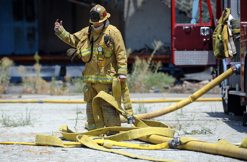 . Los Angeles County firefighters looks over water hoses during a 3-alarm fire at an abandoned warehouse near 9th Avenue and Clark Avenue on Tuesday, July 9, 2013 in City of Industry, Calif.  (Keith Birmingham/Pasadena Star-News)