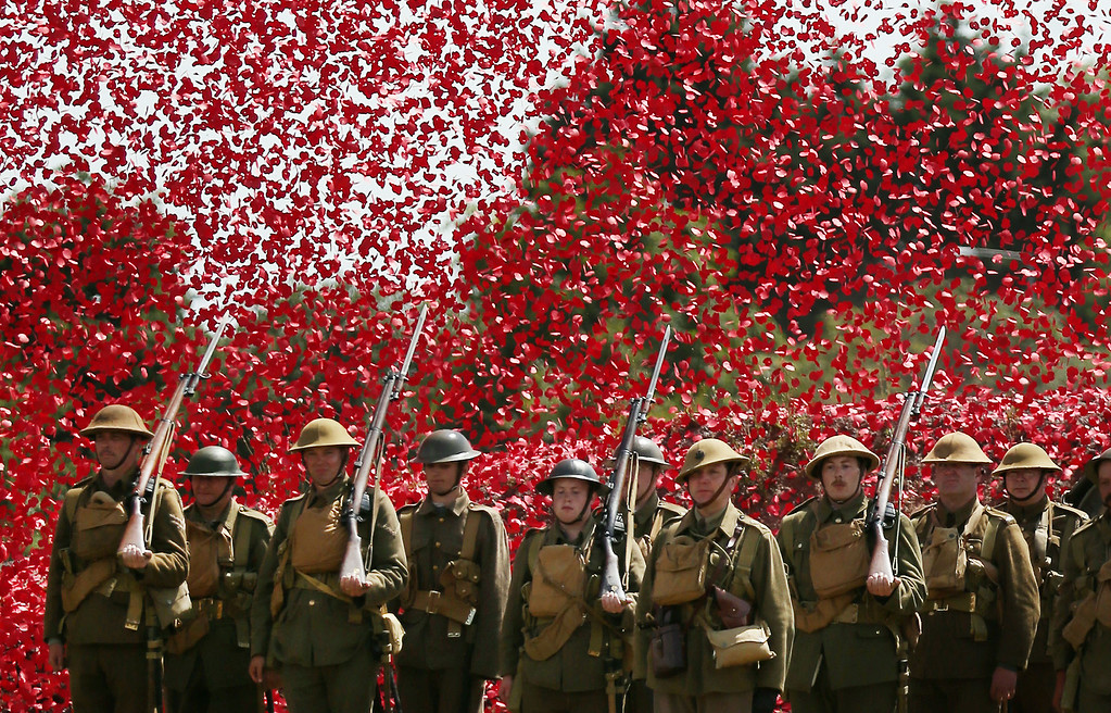 . BOVINGTON, UNITED KINGDOM - AUGUST 04:  Members of the Great War Society living history group dressed as 4th Battalion the Middlesex Regiment stand under a shower of a million poppy flowers representing the dead during a World War One centenary ceremony at the Tank Museum, Bovington on August 4, 2014 in England. Monday August 4, 2014  marks the 100th anniversary of Great Britain\'s declaration of war on Germany. In 1914 British Prime Minister Herbert Asquith announced at 11 pm that Britain was to enter the war after Germany had violated Belgium neutrality. The First World War or the Great War lasted until 11 November 1918 and is recognised as one of the deadliest historical conflicts with millions of causalities. A series of events commemorating the 100th anniversary are taking place throughout the day.  (Photo by Peter Macdiarmid/Getty Images)