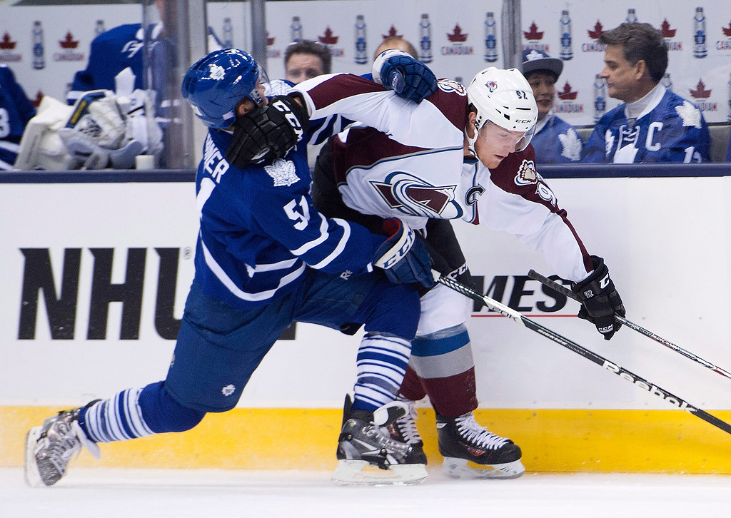 . Toronto Maple Leafs defenseman Jake Gardiner, left, slows Colorado Avalanche forward Gabriel Landeskog during the first period of an NHL hockey game in Toronto on Tuesday, Oct. 8, 2013. (AP Photo/The Canadian Press, Nathan Denette)