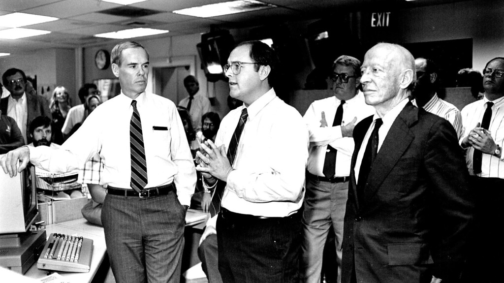 . William Dean Singleton, center, of MediaNews Group, speaks to staff of Denver Post newsroom after announcement of sale of the Post to MNG. At left is Post publisher Richard Schlosberg. At right is Singleton\'s partner Richard B. Scudder, chairman of the board of MNG. Photo taken 9/14/1987. Jerry Clevland