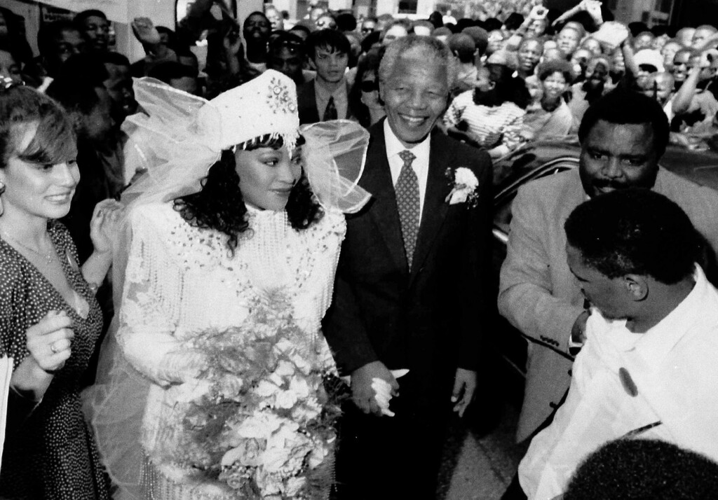 . Supporters cheer in the background as African National Congress (ANC) leader Nelson Mandela, center, holds the hand of his daughter, Zindzi, before her marriage to Zweli Hlongwae in downtown Johannesburg, South Africa, Oct. 24, 1992.  The wedding is the first of any of his children that Mandela has attended.  Mandela\'s estranged wife Winnie arrived in a separate car in the wedding motorcade.  (AP Photo/Kevin Carter)
