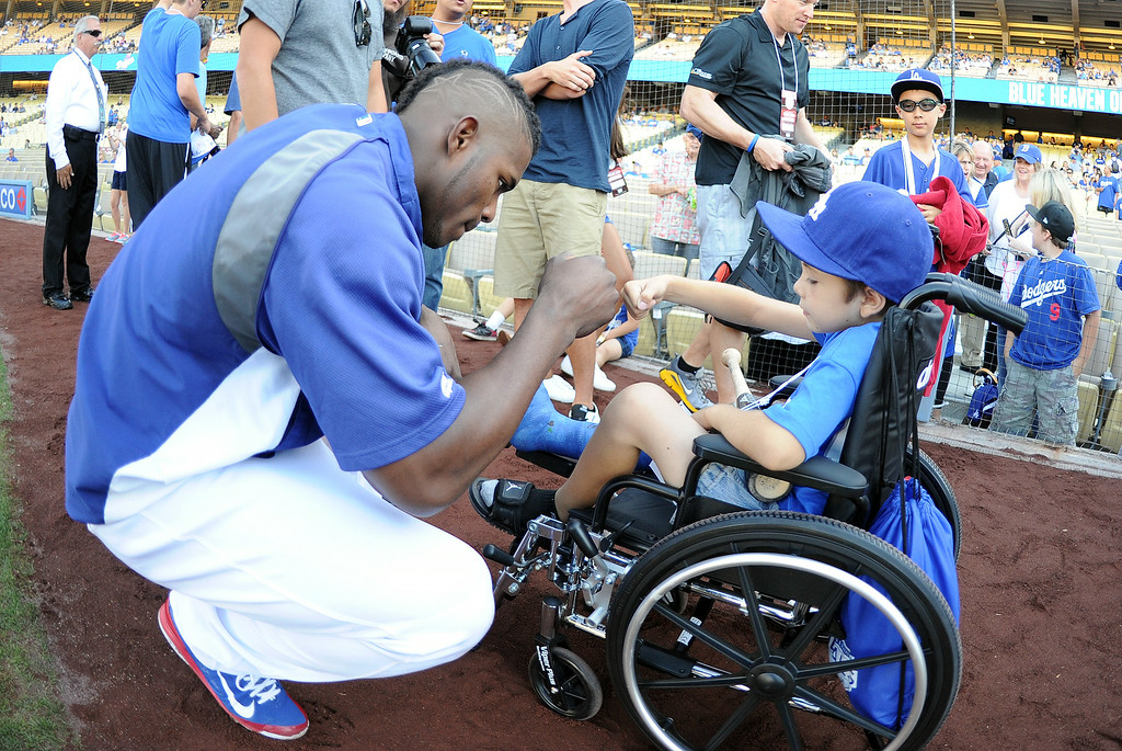 . Los Angeles Dodgers\' Yasiel Puig fist pumps 8 year-old Jeremiah Rivera of Riverside prior to a Major league baseball game between the San Diego Padres and the Los Angeles Dodgers on Saturday, July 12, 2014 in Los Angeles.   (Keith Birmingham/Pasadena Star-News)