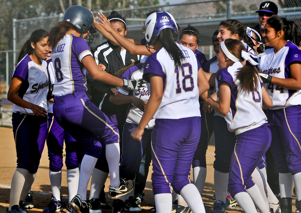 . Jurupa Hills varsity softball team congratulates Jackie Valadez (8) as she crosses home plate after hitting a two-run walk-off homerun in the bottom of the seventh inning against Citrus Valley High School on Tuesday, May 7, 2013. Jurupa Hill defeated Citrus Valley 2-3. (Rachel Luna / Staff Photographer)