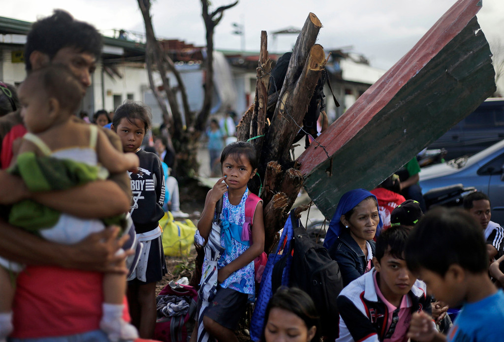. Typhoon Haiyan survivors wait for their evacuation flights at the airport in Tacloban, Philippines, Thursday, Nov. 21, 2013. Hundreds of thousands of people were displaced by Typhoon Haiyan, which tore across several islands in the eastern Philippines on Nov. 8. (AP Photo/Dita Alangkara)