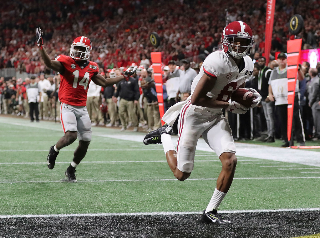 . Alabama wide receiver Devonta Smith runs into the end zone for a touchdown after catching a pass past Georgia defensive back Malkom Parrish during overtime of the NCAA college football playoff championship game in Atlanta on Monday, Jan. 8, 2018. Alabama won, 26-23. (Curtis Compton/Atlanta Journal-Constitution via AP)