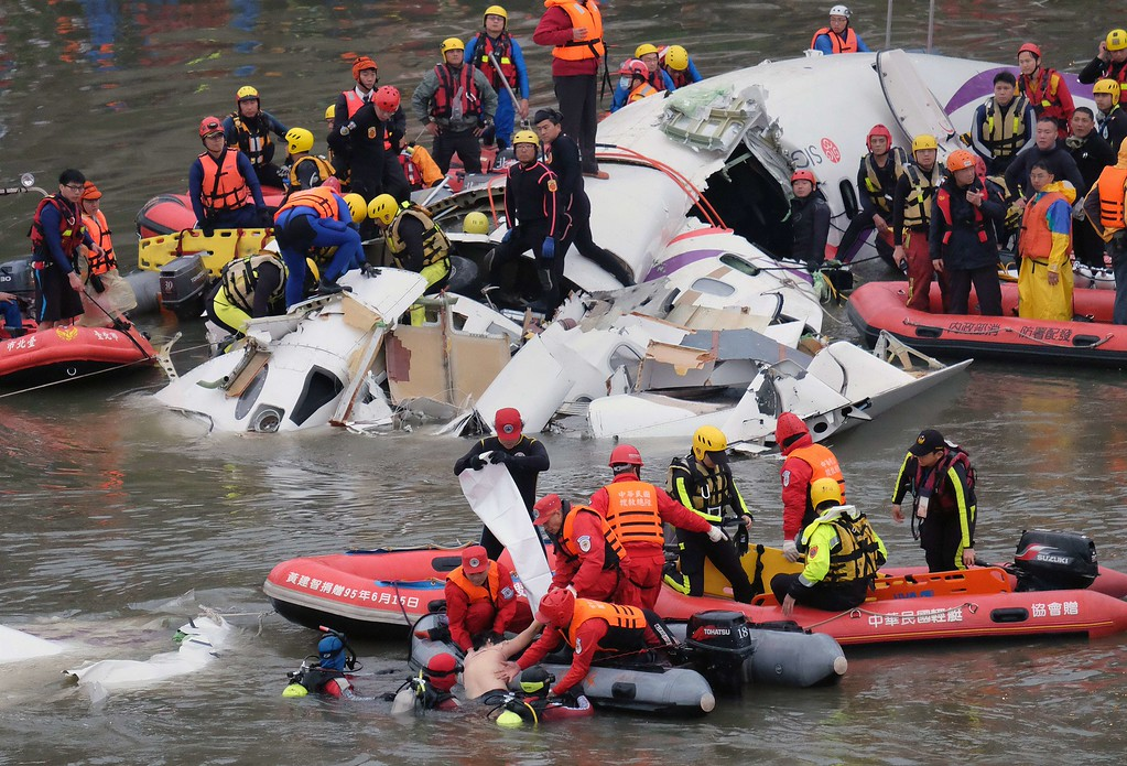 . Rescue personnel in a rubber dinghy lift a passenger (bottom C) from the waters around the wreckage of a TransAsia ATR 72-600 turboprop plane that crash-landed into the Keelung river outside Taiwan\'s capital Taipei in New Taipei City on February 4, 2015. At least 16 people were killed when TransAsia Airways Flight GE235 with 58 people on board clipped a road bridge and plunged into the river in Taiwan, in the airline\'s second crash in just seven months. AFP PHOTO / SAM YEHSAM YEH/AFP/Getty Images
