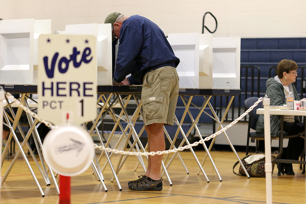 . Mike Halloran fills out his ballot at the polls in Westminster on Tuesday at the Westminster Elementary School. SENTINEL & ENTERPRRISE/JOHN LOVE