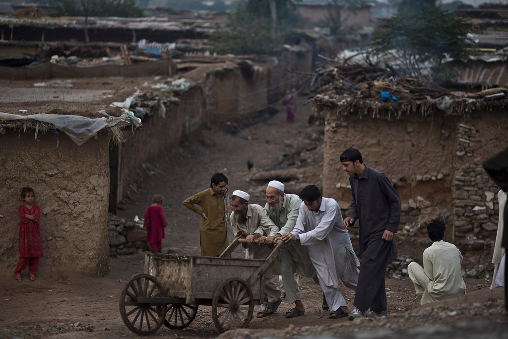 """. A young Afghan refugee helps his elders push a cart into the main road, during the Muslim holiday of Eid al-Adha, or \""""Feast of Sacrifice,\"""" on the outskirts of Islamabad, Pakistan, Thursday, Oct. 17, 2013.  (AP Photo/Muhammed Muheisen)"""