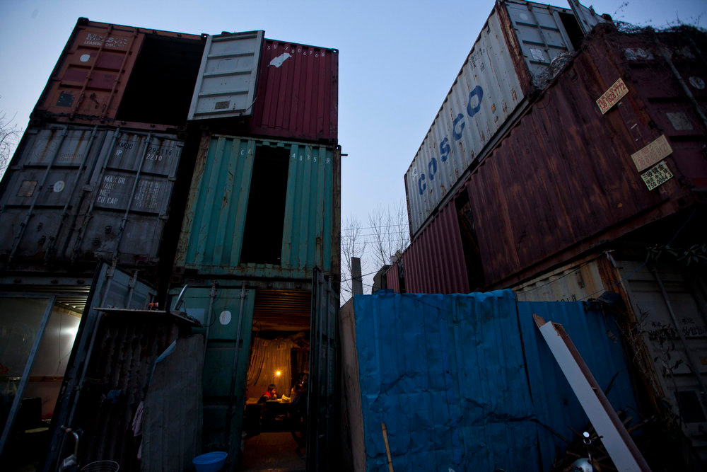 . A child (bottom) does homework inside a shipping container serving as his accommodation, in Shanghai March 4, 2013. The containers, which house different families, were set up by the landlord, who charges a rent of 500 yuan ($ 80) per month for each container. REUTERS/Aly Song