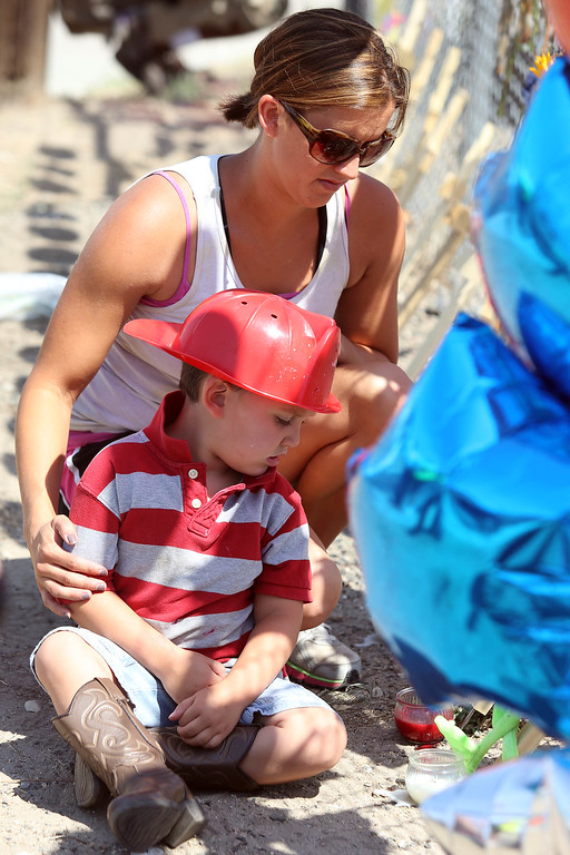 . Christine Belyea holds her three-year-old son Casen as they pay their respects to the 19 fallen firefighters in Prescott, Arizona July 2, 2013. Belyea went to school with two of the deceased Granite Mountain Hotshot firefighters. Reinforcements poured in Monday to battle a runaway wildfire which quadrupled in size overnight after killing 19 firefighters in one of the worst such incidents in US history. The Yarnell Hill fire -- which killed all but one member of a 20-strong \'hotshot\' team -- was the biggest loss of firefighters\' lives since the September 11 attacks, and the most from a US wildfire in 80 years. AFP PHOTO / KRISTA  Kennell/AFP/Getty Images