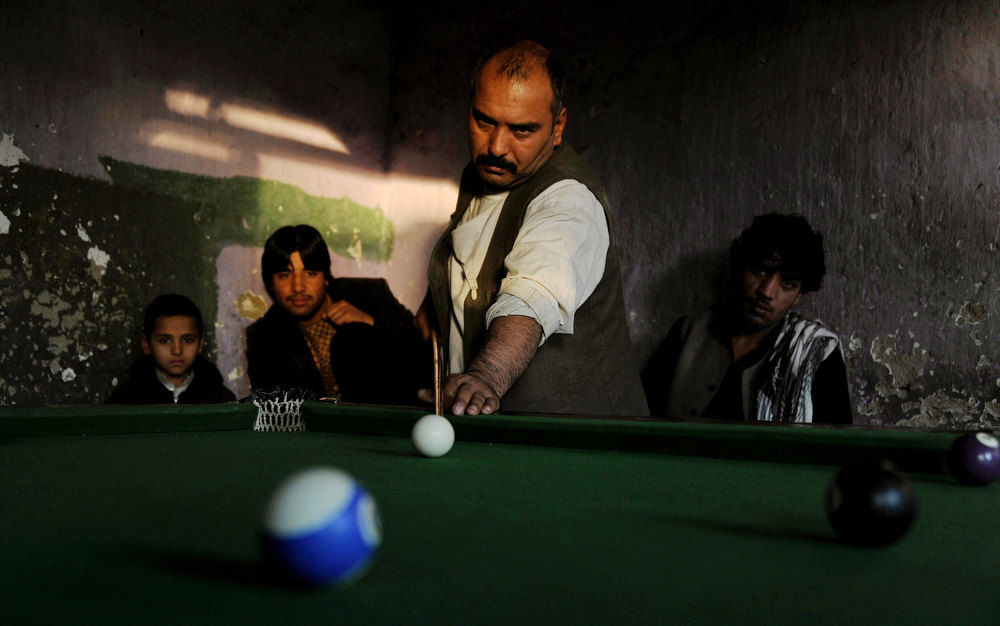 Description of . Afghan men play snooker at a billiard hall in Jalalabad on December 20, 2012. Most western games were not allowed during the years of rule by the Taliban regime.  Noorullah Shirzada/AFP/Getty Images