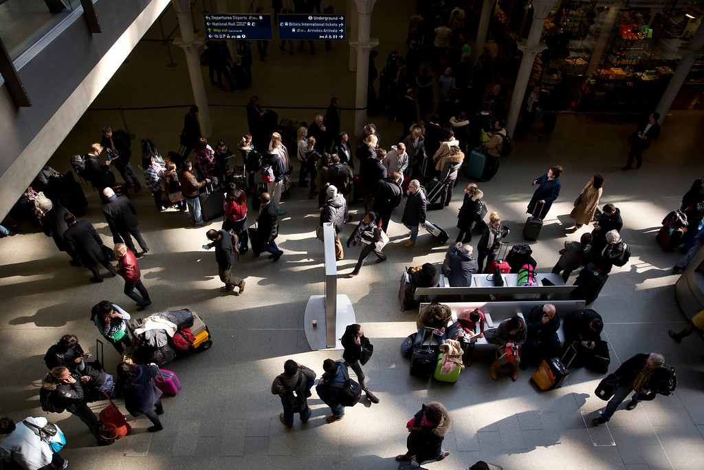 . Travelers stand in a queue at top after services were suspended on the Brussels Eurostar train route because of the attacks in Belgium, at St Pancras international railway station in London, Tuesday, March 22, 2016. Authorities locked down the Belgian capital on Tuesday after explosions rocked the Brussels airport and subway system, killing a number of people and injuring many more. (AP Photo/Matt Dunham)