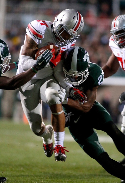 . Ohio State\'s Jalin Marshall, center, rushes against Michigan State\'s Kurtis Drummond (27) and R.J. Williamson, left, during the second quarter of an NCAA college football game, Saturday, Nov. 8, 2014, in East Lansing, Mich. (AP Photo/Al Goldis)