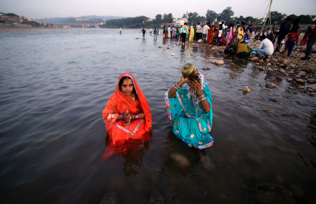 . Hindu devotees perform rituals at sunset in the Tawi River during Chhath Puja festival in Jammu, India, Friday, Nov. 8, 2013.  (AP Photo/Channi Anand)
