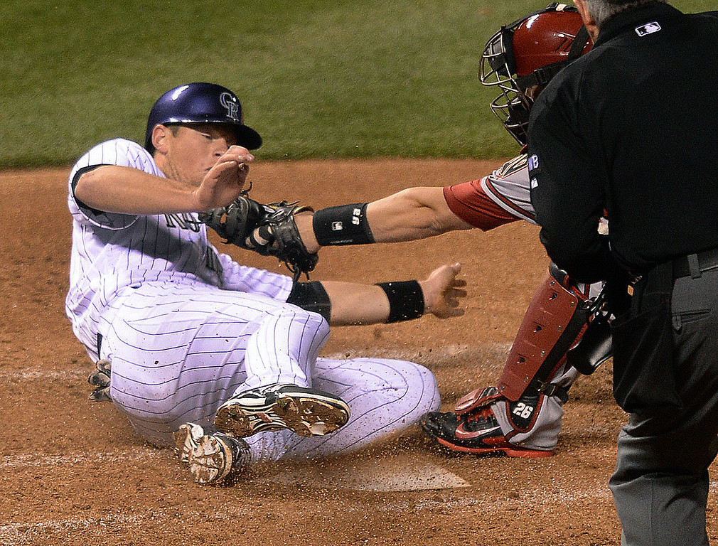 . DENVER, CO - APRIL 5:  Colorado baserunner DJ LaMahieu (9) scored from first base on a single by Carlos Gonzalez in the fifth inning. LaMahieu successfully slid under the attempted rag by Arizona catcher Miguel Montero. The Rockies took 5-4 lead with the run. The Colorado Rockies hosted the Arizona Diamondbacks Saturday night, April 5, 2014 in Denver. (Photo by Karl Gehring/The Denver Post)