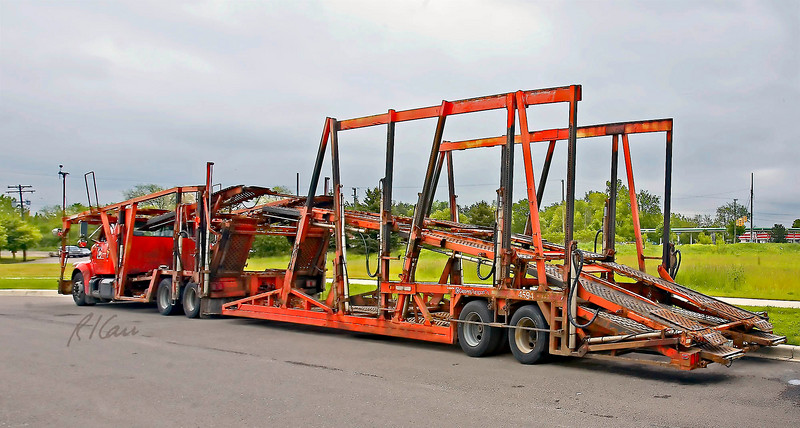 Trucks/autos/cars: International semi-truck tractor powered hydraulically adjustable two-level automobile carrier. Tractor is outfitted as a carrier itself, towing an integrated auto carrier trailer. The segments of the upper level are each hydraulically adjustable to fit auto models and loading conditions. Ann Arbor, Michigan May 2006